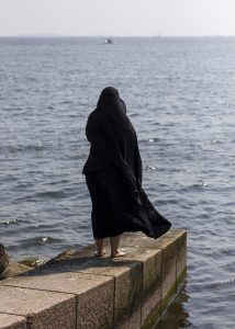 Mustaan viittaan pukeutunut nainen katsoo merelle
