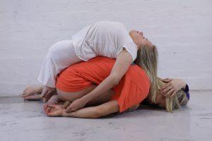 Yksi tanssija kyyristynyt lattialle, toinen tanssija hänen selkänsä päällä