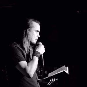 Jussi Kiova, kädessään kirja ja mikrofoni